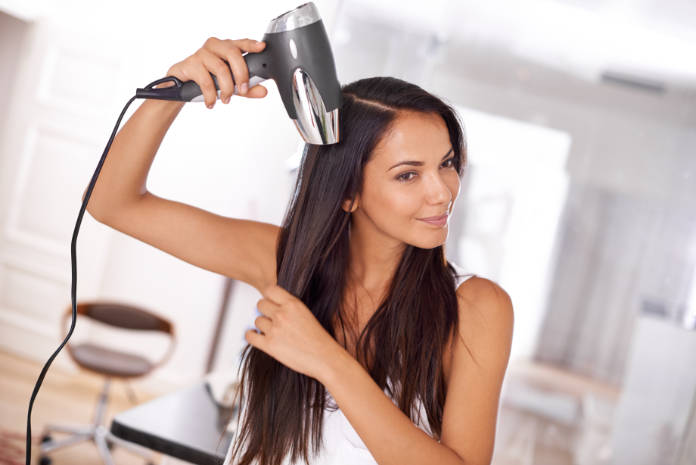 a beautiful young woman blow drying her