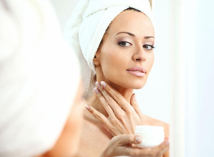 Woman applying neck cream