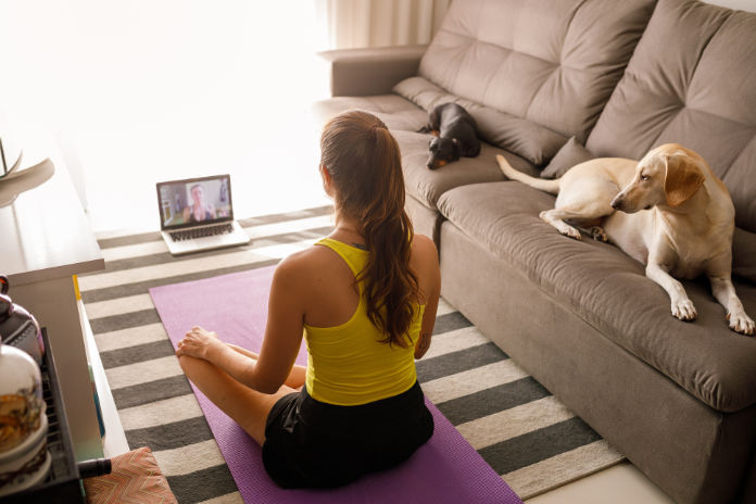 Woman practicing yoga with trainer via video conference.