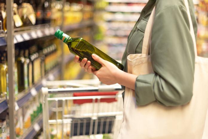 Super market shopping girl choosing bottle of oil