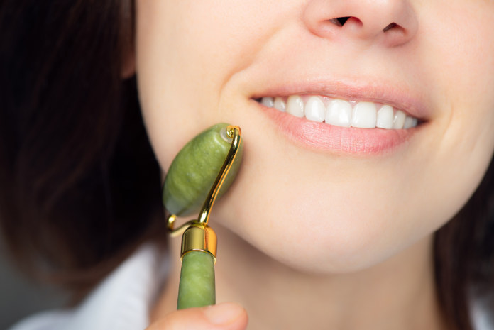 Close up of young woman with jade face roller. She is doing beauty facial massage therapy