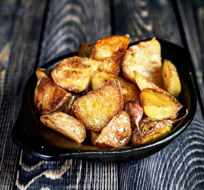 Delicious baked potato wedges with garlic with husk in black rustic plate on dark wooden table. Appetizing crisp. Traditional garnish or side dish for Christmas dinner. Country-style roasted potatoes