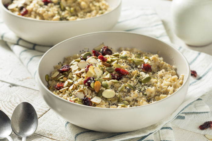 Healthy Organic Superfood Oatmeal Breakfast with Chia Seeds Pumpkin Almonds Cranberries Hemp