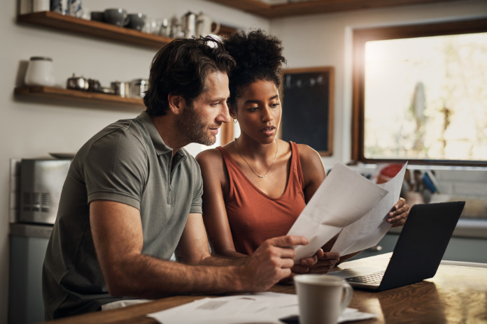 affectionate young couple going through paperwork while doing their budget at home