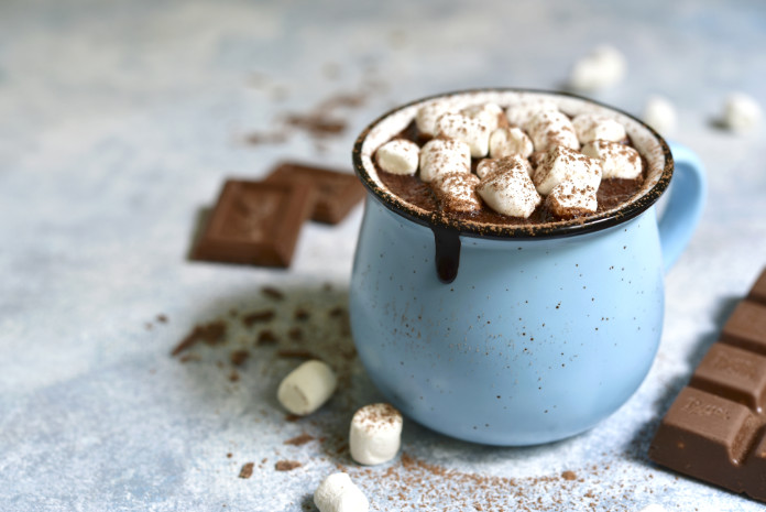Homemade hot chocolate with mini marshmallow in a blue enamel mug on a light slate background.