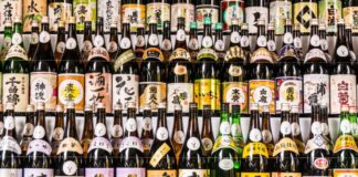 Large collection of Japanese sake bottles with multiple colored labels arranged on shelfs taken at temple in Tokyo.