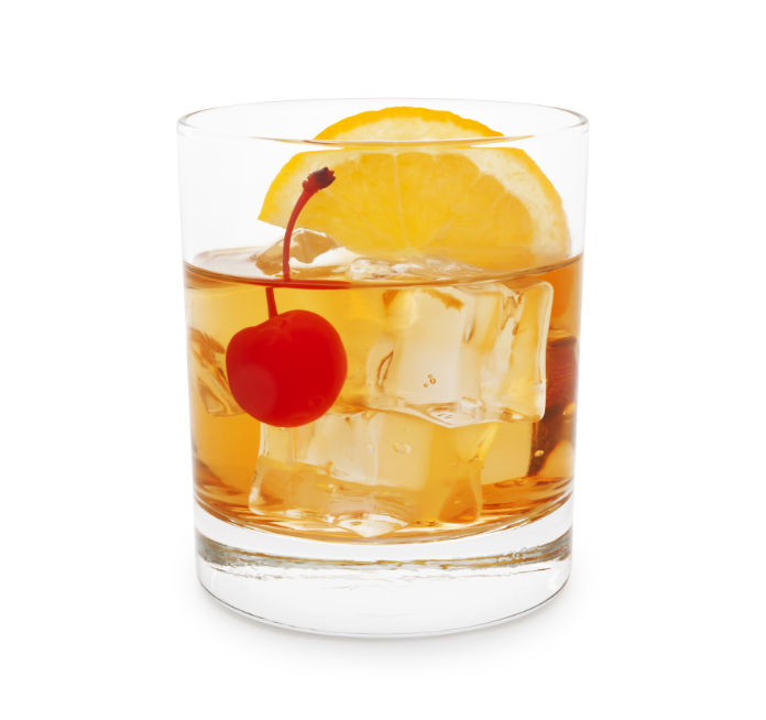 Old-fashioned cocktail with cherry and orange slice isolated on white