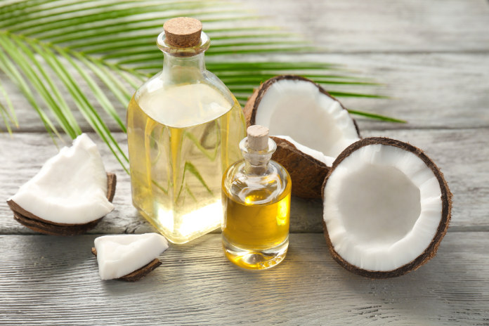 Bottles with fresh coconut oil on wooden table