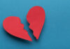 Broken paper heart on blue background