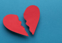 Broken paper heart on blue background