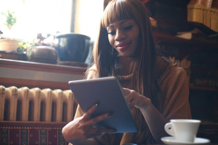 African American woman working on digital tablet and drinking coffee.