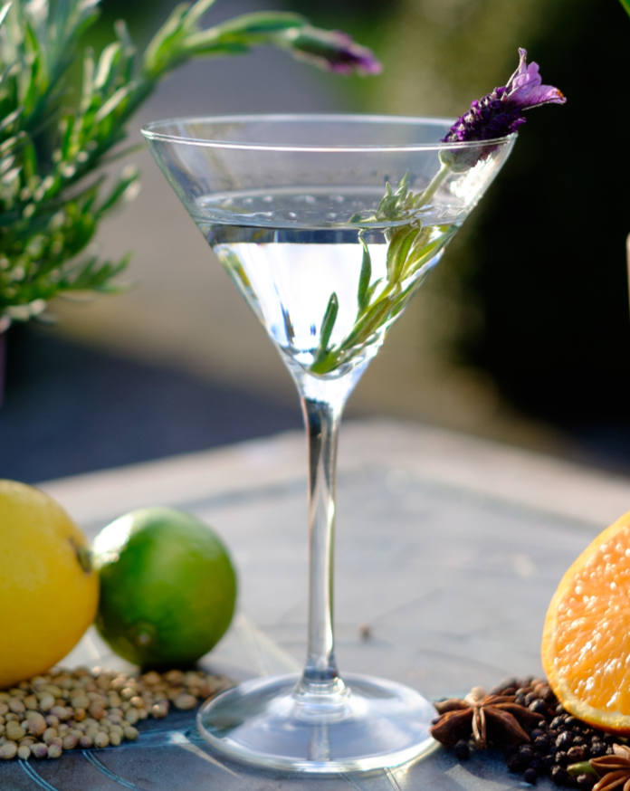 Alcoholic summer drink in a garden with fruit, flowers and spices on a sun dial