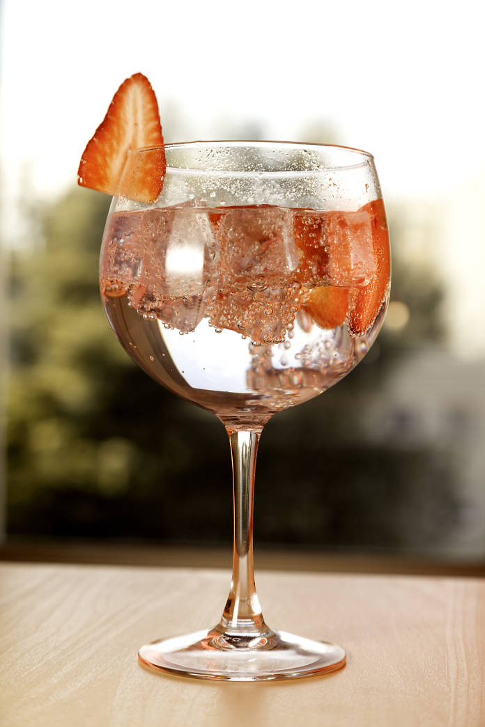 Gin tonic with strawberry  on natural background