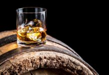 Whisky facts Glass of whisky with ice on old wooden barrel.