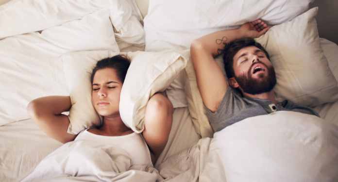 Shot of a young woman covering her ears with a pillow while her husband snores in bed