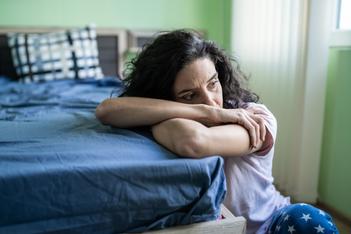 Mid adult woman sitting home alone, worried.