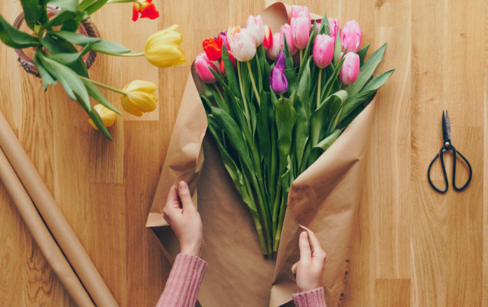 Top view of woman's hands creating a bouquet of tulips on a wooden table