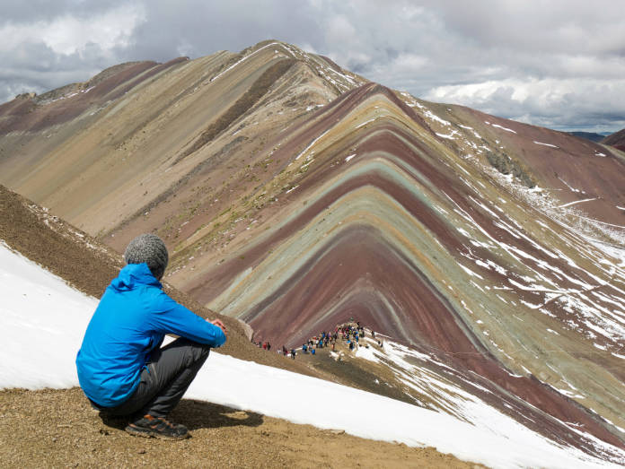 man sitting and enjoying rainbow mountain landscape with hill, mountains, seven colors at rainbow mountain, cusco, peru
