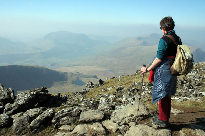 A lone hiker admires the view from Snowdon, North Wales