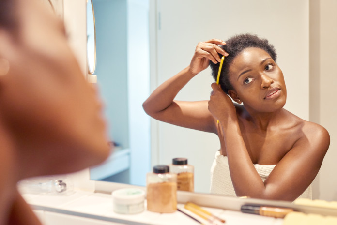 Treating damaged relaxed hair Cropped shot of a young woman combing out her hair while looking in the bathroom mirror