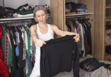 Woman reorganizing her wardrobe in her bedroom