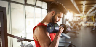 Fasted workouts – Determined male working out in gym lifting weights