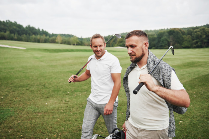 Two male friends playing golf