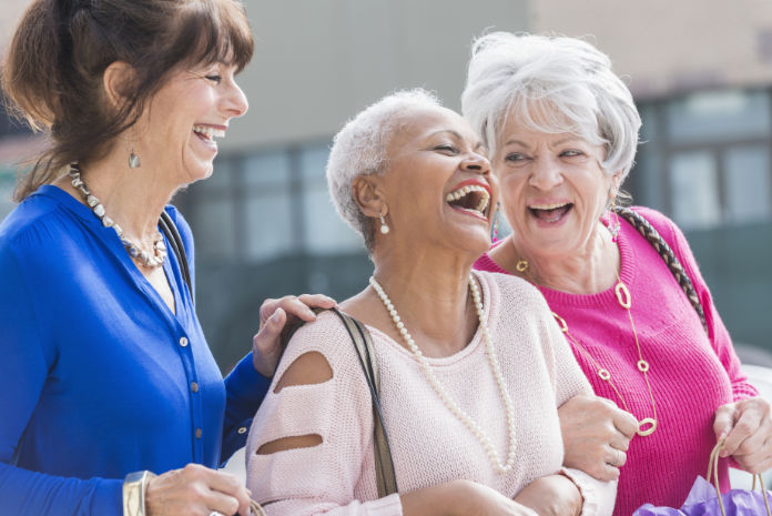 A group of three multi-ethnic senior women in their 60s and 70s standing outdoors, laughing.