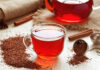 Herbal tea benefits Cup of healthy traditional herbal rooibos red beverage tea with spices on vintage wooden table