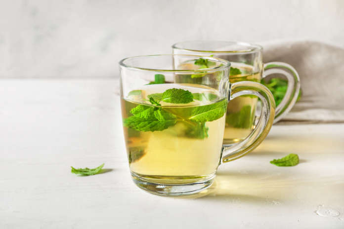 Herbal tea benefits Peppermint tea in clear glass cups on white wooden table on white background.