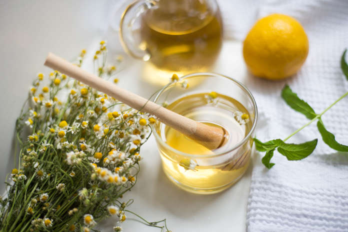 Herbal tea benefits Transparent cup with chamomile tea and chamomile flowers