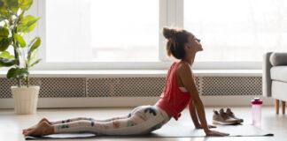 Calm mindful woman practising yoga asana at home