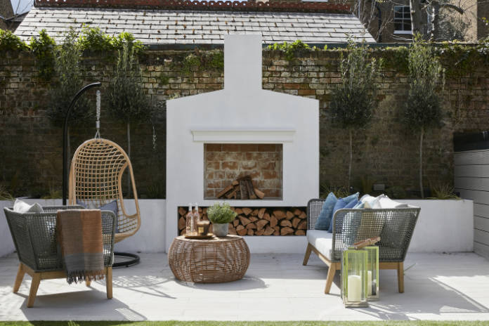 Outdoor living outdoor living room featuring a trendy hanging chair, lounge furniture and open fireplace