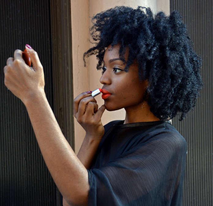 Nigerian model, fashion blogger designer & makeup artist touching up her lipstick in Greenwich Village, Manhattan, New York City
