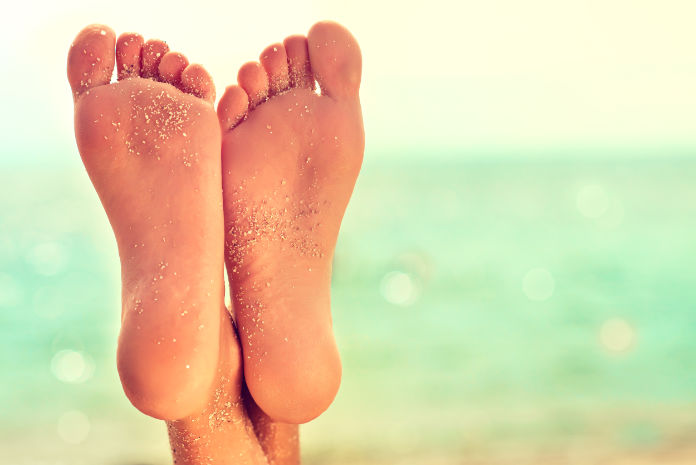Well-groomed crossed woman's feet covered by sand of tropical beach