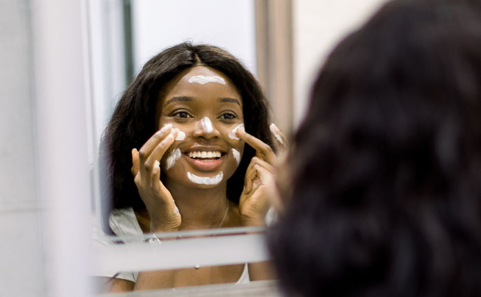 Portrait of attractive African American girl standing near the mirror, applying clay cosmetic mask on her beautiful face skin, enjoying beauty procedures