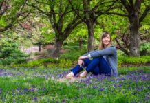 Managing chronic pain woman sat in bluebells