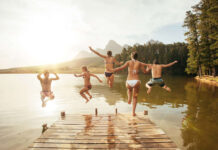 Holiday advice Friends leaping into a lake