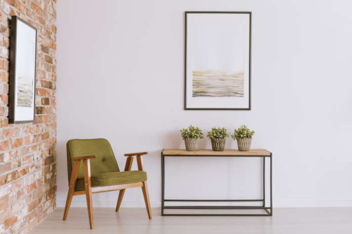 Bright painting above cabinet with plants in vintage living room with classic armchair