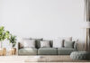 Scandinavian home decor with green couch, rattan pot and floor lamp