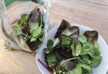 A bag of salad leaves on a table