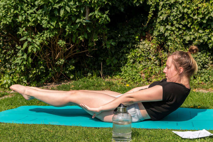 A lady undergoing exercise in her garden; example of wellbeing