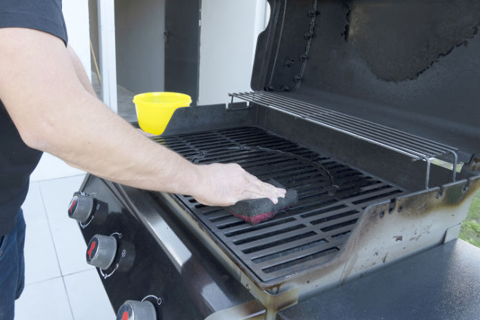 The male hand cleans the black grill with a soft brush.