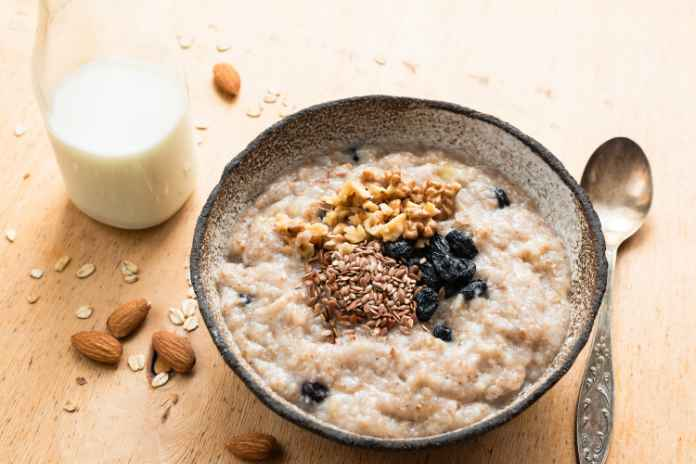 Breakfast porridge oats in bowl topped with flaxseedson wooden table.
