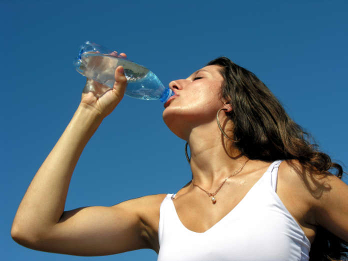 Thirst. Young woman drinks cold water in hot day