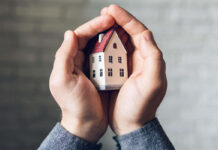 Someone holding a toy house representing a burglar-proof home