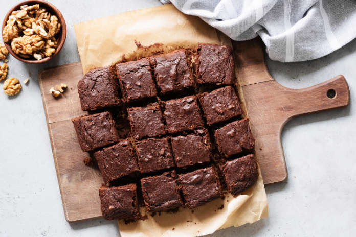 Chocolate brownie squares with walnuts on cutting board