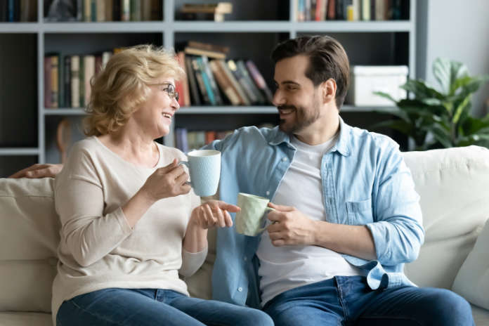 Smiling pleasant middle aged senior mother chatting with grown up son, relaxing together on comfortable sofa with cups of tea in hands, sharing life news, gossiping or joking on weekend at home.