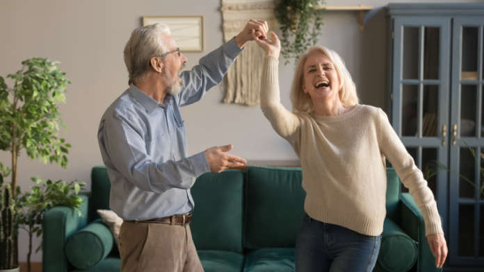 Joyful active old retired romantic couple dancing laughing in living room