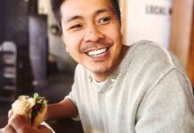A happy man eating a burger, representing a